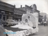 [Putnam County Fair/Homecoming?] Queen in a parade Float in Front of Maddux, Proffitt...
